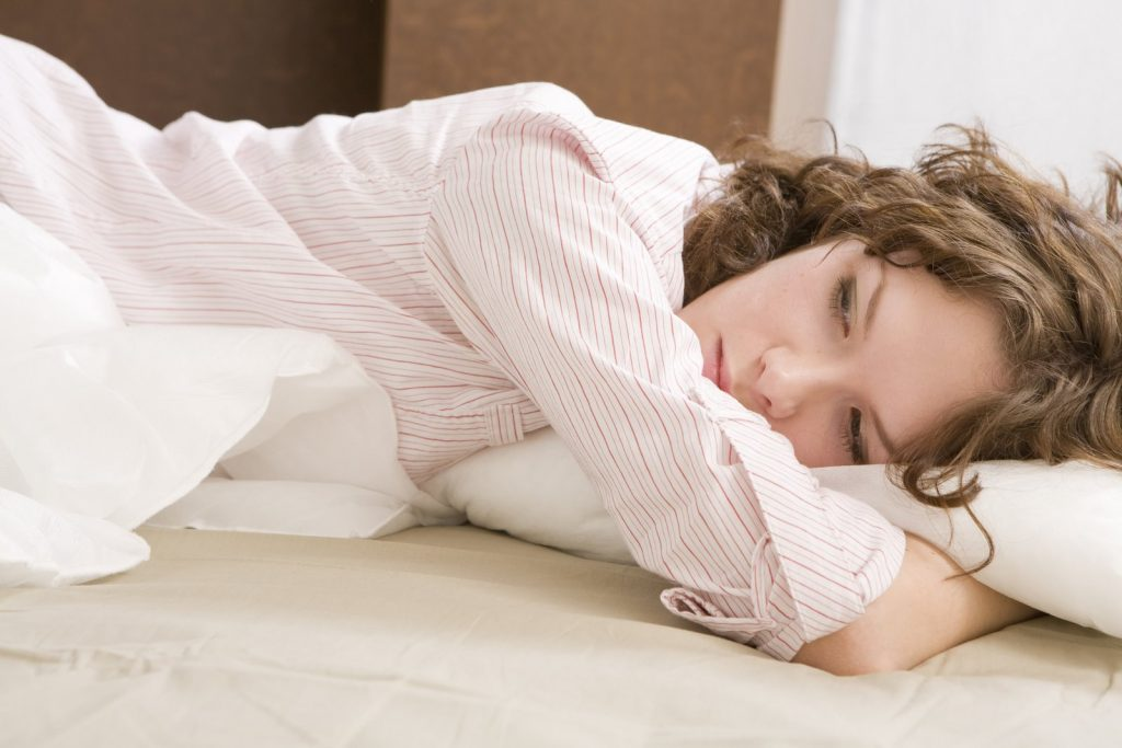 attractive thoughtful brunette curl woman with a pillow on the bed Woman`s problem